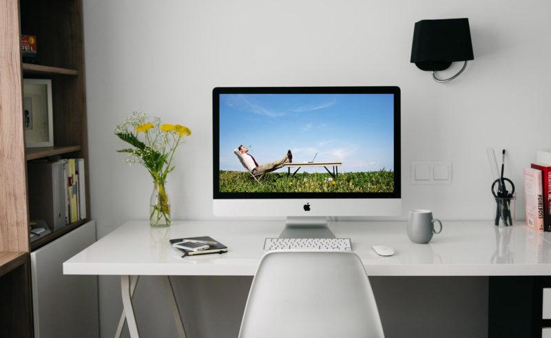 endlich sorglos online: Entspannter Geschäftsmann in einem Liegestuhl auf einer Blumenwiese liegend